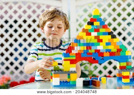 Little blond child playing with lots of colorful plastic blocks. Adorable preschool kid boy wearing colorful shirt and having fun with building big castle and creating a house.