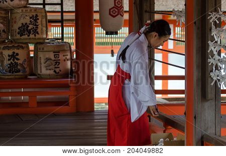 Shrine Maiden Remove The Japanese Omikuji Or Sacred Lottery  In Itsukushima Shrine. Is A Shinto Shri