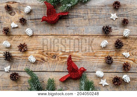bird toys and pine cones to decorate christmas tree for new year celebration with fur tree branches on wooden table background top veiw mockup