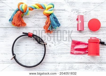 care about pet with collar and red grooming equipment on white wooden table background top view