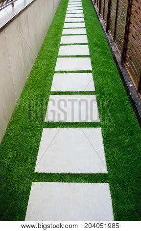 Pathway in garden, green lawns with bricks pathways