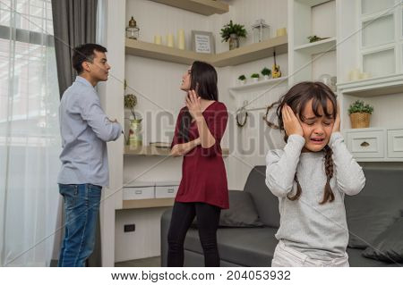 Little girl is crying because her parents quarrel.