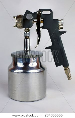 Air paint gun with metal can on the light background
