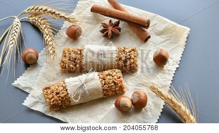 two muesli bars with filbert nuts anise star cinnamon sticks wheat ears on backing parchment background