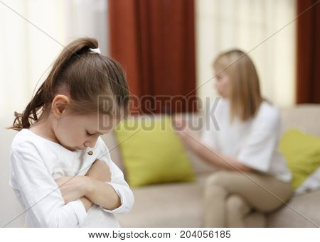 Sadness Young Girl. Portrait Of Bored Daughter With Mother Using Cellphone On Bed.