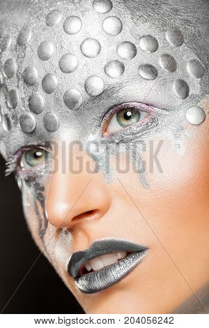 Art fantasy makeup. Close-up of young woman with fashion silver makeup with rivets
