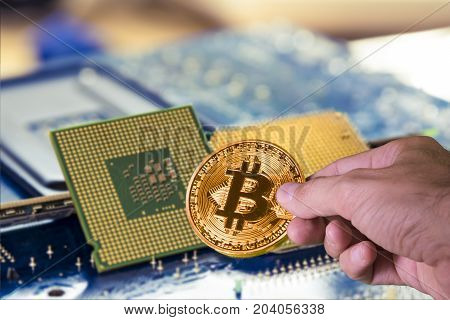 Hand holding a bitcoin and Technology background with computer processors CPU concept and blue circuit, board texture.