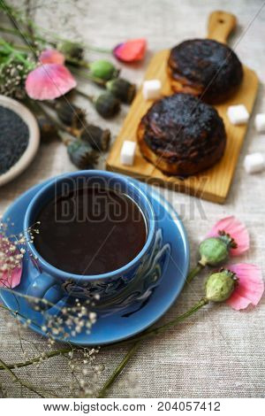 a fine breakfast a mug of tea fresh rolls with poppy seeds and poppy flowers.