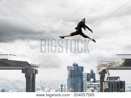 Business woman jumping over gap in concrete bridge as symbol of overcoming challenges. Dark sky and cityscape on background. 3D rendering.