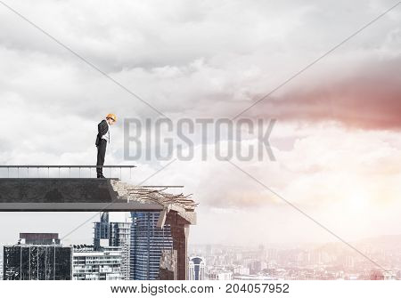 Young engineer in suit and helmet looking down while standing on broken bridge with cityscape and sunlight on background. 3D rendering.
