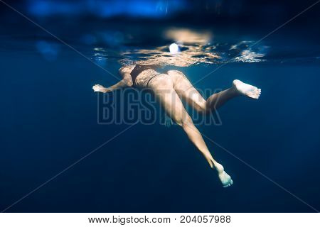 Woman swimming in blue sea. Underwater view