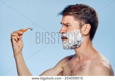 the man in the shaving foam looks at the razor.