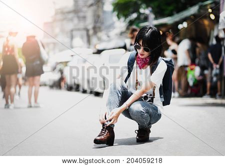 A beautiful girl Hipster walking down the street through the market wearing a hat with a backpack jeans and a T-shirt and shoelaces special tie boots fashion sunglasses. Urban style tourist.