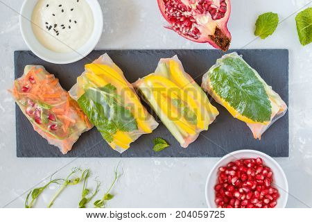 raw spring rolls with vegetables on slate concrete background