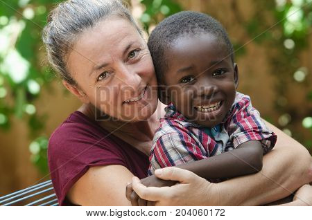 Adoption symbol - Woman adopts a little African boy