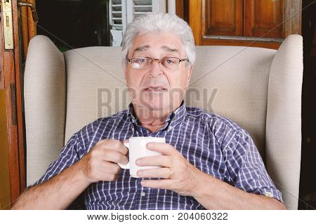 Portrait of an old man having a cup of coffee and sitting on couch. Indoors.