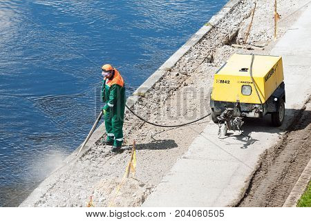 VILNIUS LITHUANIA - MAY 02 2016: Construction worker cleaning concrete with the help of industrial compressor on the riverside of Neris river in Vilnius Lithuania.