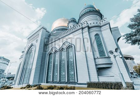 Wide-angle view from bottom side of The Grand Cathedral Mosque made of stone: golden dome and spires loudspeaker for prayerful broadcasting and security camera in foreground Moscow Russia