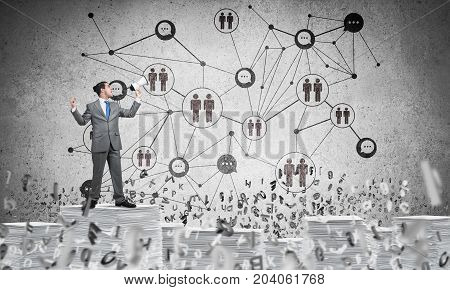 Businessman with speaker in hand standing among flying letters with social network structure on background. Mixed media.