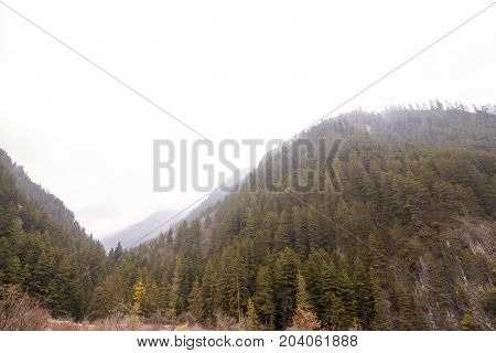 Green mountains against the blue sky. Mountain river landscape of mountains. Foggy sky above the stone mountains