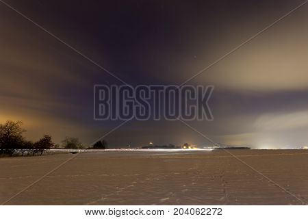 View over a wide snow covered field with a distant street at night. Taken in Lachen-Speyerdorf in Rhineland-Palatinate, Germany