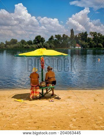 Women on the village beach under an yellow beach umbrella. Riverside
