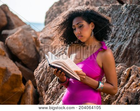 Beautiful African woman reading book on the rocks beach, pretty black female enjoying summer vacation relaxing outdoor
