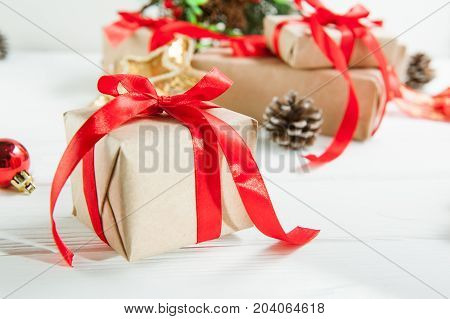 Christmas Holidays Composition With Gifts In Craft Paper With Red Satin Ribbon On The White Wooden B
