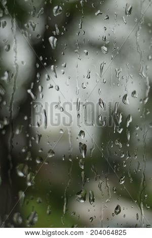 Close up of window pane with rain drops looking out at blurred background of trees and grey sky