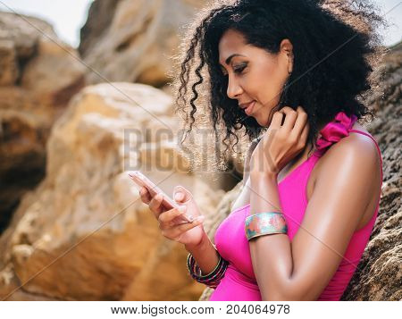 Portrait of a young african american black woman sitting on rocks beach using smartphone against blue sky. Adolescent technology lifestyle outdoors.
