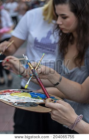 TIMISOARA ROMANIA - SEPTEMBER 8 2017: Girls that painting at the street inside the CheckART Carnival organized by the City Hall Timisoara. Liberty Square.