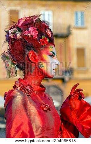 TIMISOARA ROMANIA - SEPTEMBER 8 2017: Portrait of living statue of a woman multicolor dressed and present on the street CheckART Carnival organized by the City Hall Timisoara. Union Square.