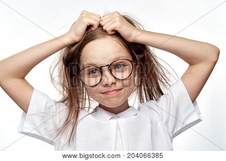a girl with glasses holds on to her head.