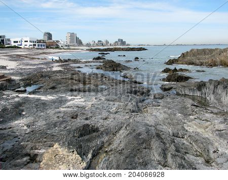 LANDSCAPE, WITH HUGE ROCKS IN THE FORE GROUND AND HIGH RISE BUILDINGS IN THE BACK GROUND
