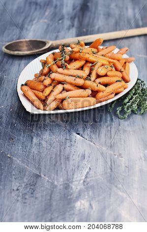 A rustic wooden spoon filled with Honey Glazed Baby carrots. Extreme shallow depth of field with selective focus on foreground.