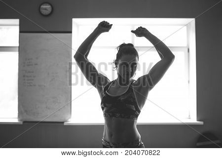 Beautiful girl with embossed muscles, stands with her hands up. Silhouette photo black and white against the window in the gym