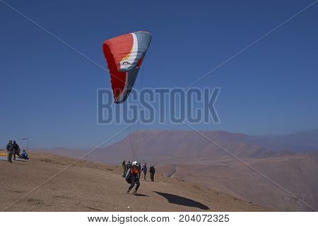 Iquique, Tarapaca Region, Chile - August 20, 2017: Paraglider taking off over the coastal city of Iquique on the northern coast of Chile.