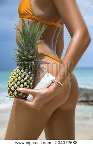 Close-up beautiful luxury slim back of a beautiful woman in a swimsuit on the beach the ocean. Sexy tanned body pineapple and sunblock cream in hands. Rest on a tropical island. Sexy buttocks