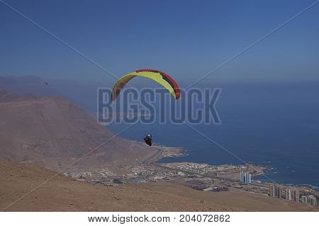 Iquique, Tarapaca Region, Chile - August 20, 2017: Paraglider over the coastal city of Iquique on the northern coast of Chile.