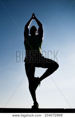 Athlete Man Silhouette Posing Outdoors On Clear Blue Sky