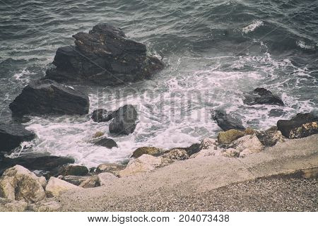 the waves crash on the huge rocks in the sea