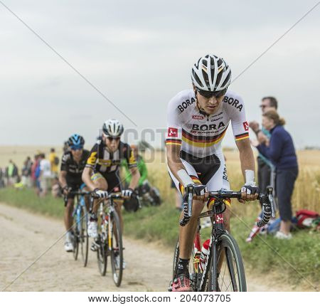 QuievyFrance - July 07 2015: Environmental portrait of the German cyclist Emanuel Buchmann of Bora-Argon 18 Team inside the peloton riding on a cobblestoned road during the stage 4 of Le Tour de France 2015 in Quievy France on 07 July2015.