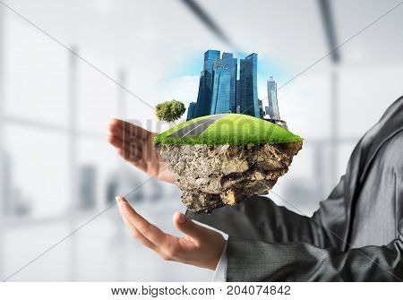Closeup of business woman in suit keeping green island with skycraper city in her hands with office view on background. Mixed media.