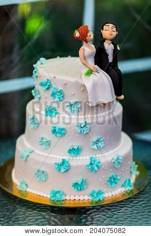 Funny figurines suite at a luxury wedding white cake.