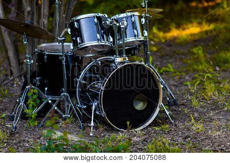 Set of black battery drum set under the tree on the grass.
