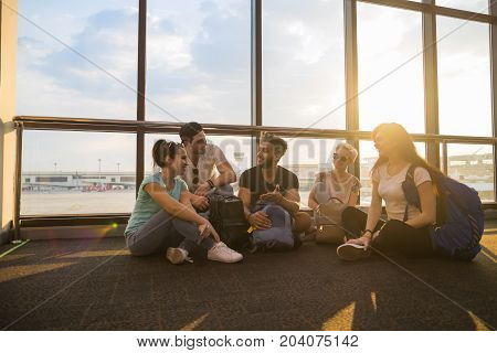Young People Group Sitting On Floor In Airport Lounge Windows Waiting Departure Speaking Happy Smile Mix Race Friends Flight Delay