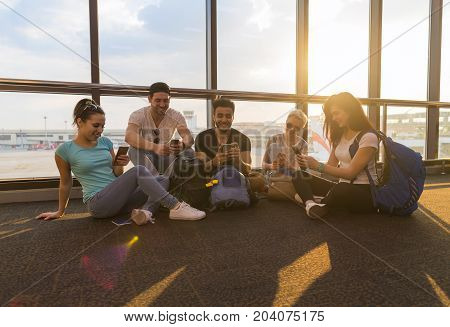 Young People Group Sitting On Floor Airport Lounge Waiting Departure Use Cell Smart Phone Chatting Mix Race Friends Happy Smile Flight Delay