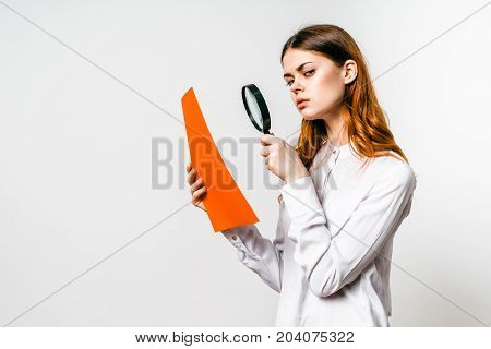 A woman with a magnifier looks skeptically at documentationon white