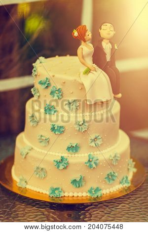 Funny figurines suite at a luxury wedding white cake. Vintage tone