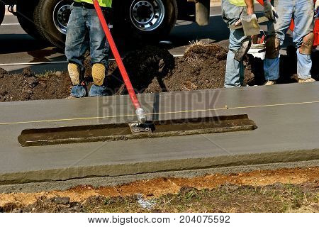 Construction worker uses bull float across freshly poured concrete on a sidewalk project